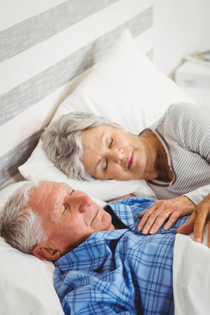 pareja durmiendo: par mayor que duerme en cama en el dormitorio