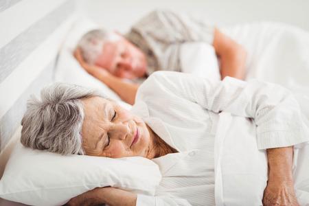 寝室のベッドに寝ているシニア カップル 写真素材