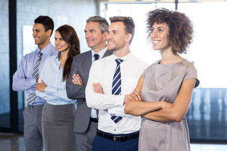 mani incrociate: Confident business team standing in office with their hands crossed