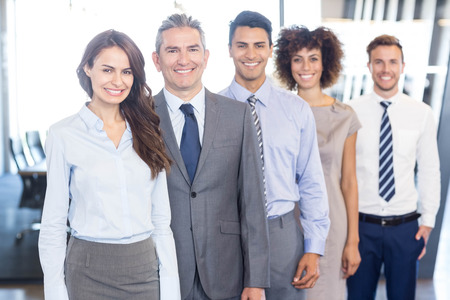 Confident business team smiling and standing in a row in office Stock Photo