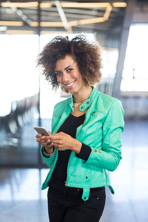 phone professional: Young woman using mobile phone in front of conference room in the office
