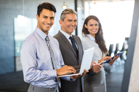 Businesspeople standing in a row and using mobile phone, lap top and digital tablet in office Stockfoto