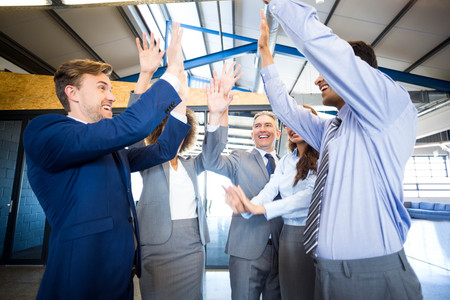 standing together: Happy business team high fiving in office Stock Photo