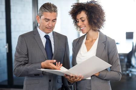 looking into: Businessman looking into a document and interacting with colleague