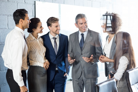interacting: Businesspeople interacting with each other in conference room