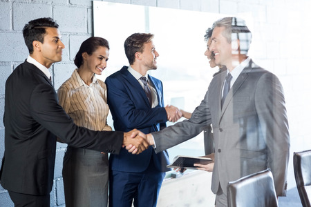interacting: Businessman interacting and shaking hands with team in office