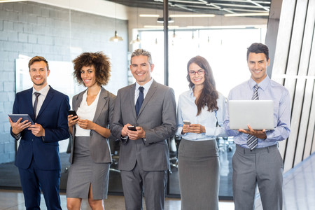 lap top: Businesspeople standing in a row and using mobile phone, lap top and digital tablet in offic Stock Photo