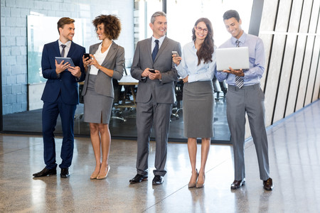 lap top: Businesspeople standing in a row and using mobile phone, lap top and digital tablet in office Stock Photo