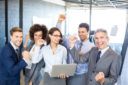 Happy business team celebrating a success in office