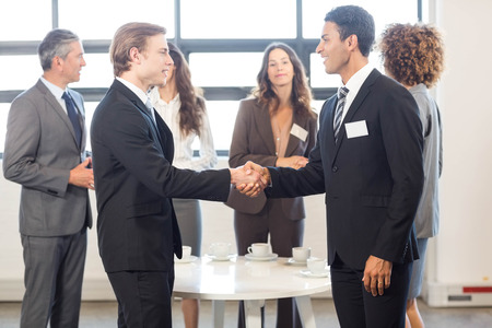 interacting: Business team standing together and interacting in office