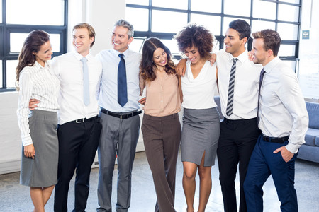 arms around: Businesspeople standing together with arms around each other in office