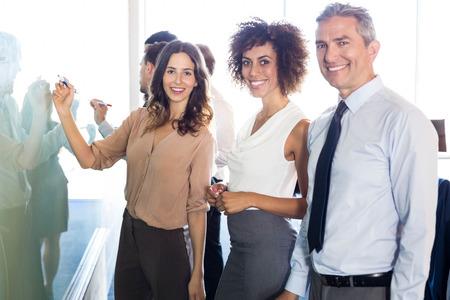 Portret van ondernemers glimlachen terwijl het schrijven op wit bord in het kantoor