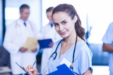 medical report: Female doctor writing a medical report and colleagues standing behind