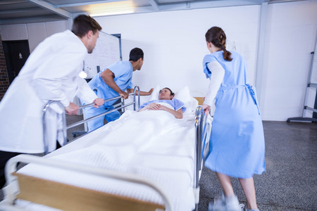hospital patient: Doctors standing near patient bed in hospital