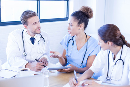 medical professional: Medical team discussing in meeting at a conference room