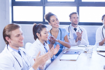 applauding: Medical team applauding and smiling in meeting at conference room
