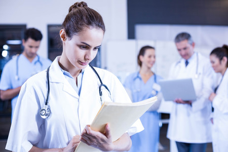 medical report: Female doctor checking a medical report and colleagues standing behind Stock Photo