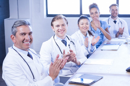 Portrait of medical team applauding and smiling in meeting at conference room