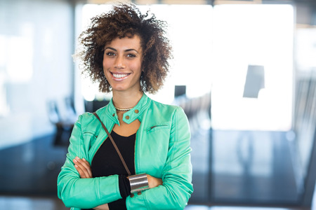 confident business woman: Portrait of young woman smiling in office