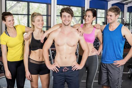 Atléticos hombres y mujeres posando juntos en el gimnasio crossfit