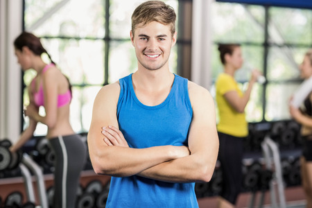 athletic women: Muscular man posing with athletic women behind at crossfit gym Stock Photo