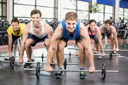 women working out: Athletic men and women working out at crossfit gym