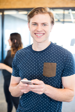 text messaging: Portrait of man text messaging on smartphone in office