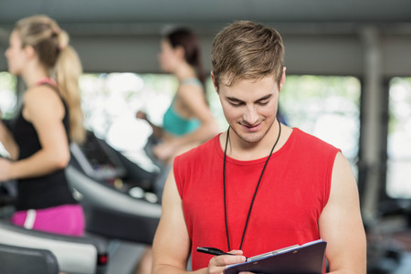 adult  body writing: Male trainer smiling to camera in crossfit gym