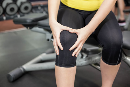 human knee: Fit woman having knees pain at gym