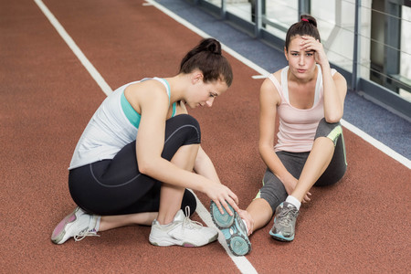 Fit woman having an ankle pain in crossfit Stock Photo