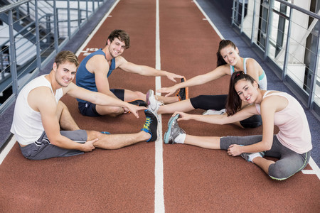 athletic women: Four athletic women and men stretching on running track