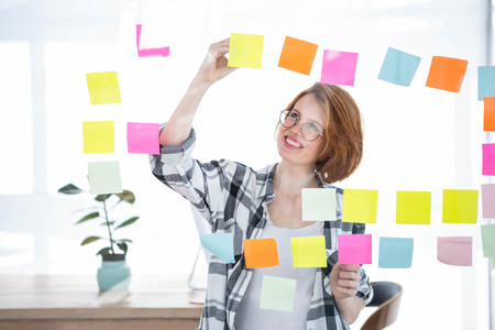 strawberry blonde: smiling hipster woman in her office, sticking notes to a wall