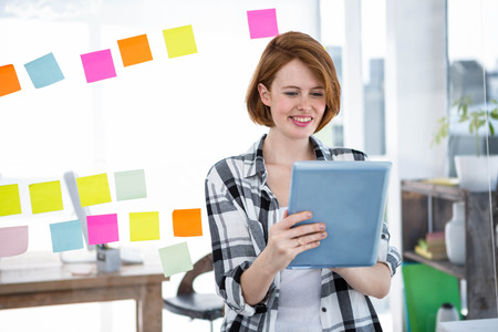 strawberry blonde: smiling hipster woman, sitting at her desk on her taableet