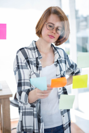 strawberry blonde: thoughtful hipster woman, sitting at her desk reading notes