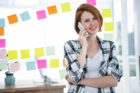 strawberry blonde: smiling hipster woman, standing in front of notes, making a phonecall Stock Photo