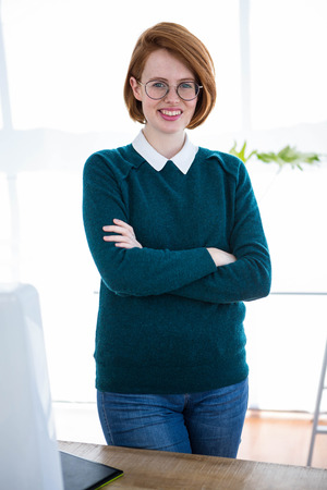 strawberry blonde: smiling hipster business woman standing in her office with her arms folded