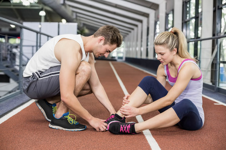 sports club: Muscular woman having an ankle injury in crossfit gym