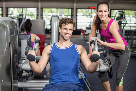 Trainer woman helping athletic man in gym Stock Photo