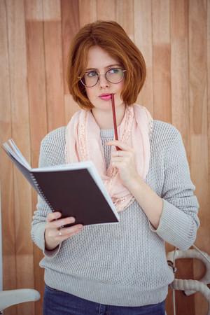 mujer pensativa: mujer inconformista pensativa que sostiene una libreta y un l�piz de pie sobre un fondo de madera Foto de archivo
