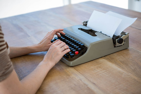 typewrite: female hands typing on a typewrite that is on a wooden desk