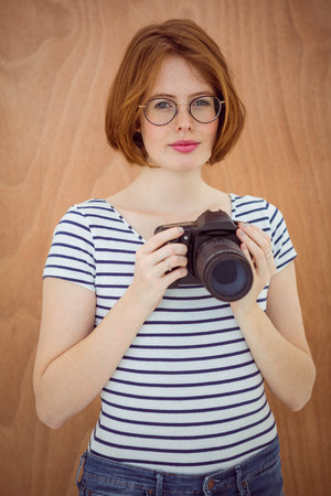 strawberry blonde: smiling hipster woman holding a digital camera against a wooden background Stock Photo