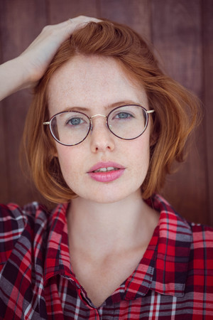 strawberry blonde: beautiful hipster woman staring into the camera against a wooden background
