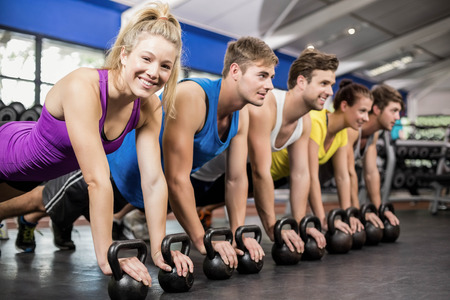 plank position: Fitness class in plank position with dumbbells in gym