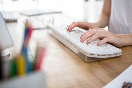 womans hands: womans hands typing on a keyboard in an office Stock Photo