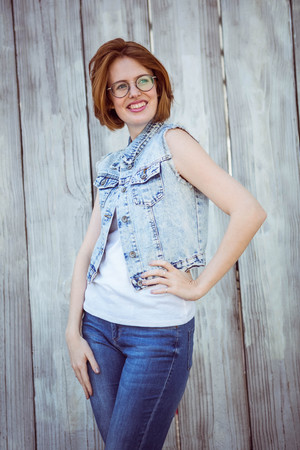 strawberry blonde: smiling hipster woman with her hand on her hip, against a wooden background