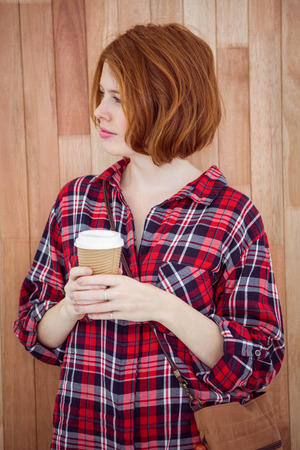 strawberry blonde: beautiful hipster woman holding a coffee cup against a wooden background