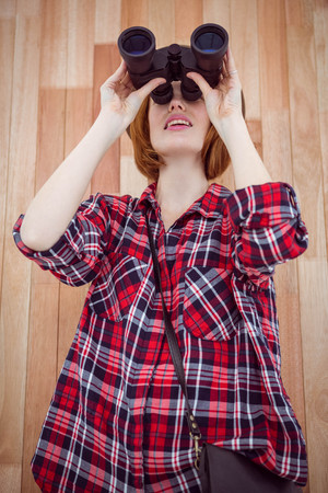 strawberry blonde: smiling hipster woman looking through binoculars against a wooden background Stock Photo
