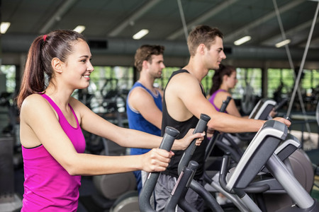 elliptical: Fit people on elliptical bike at gym