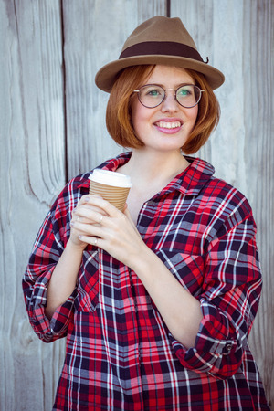 strawberry blonde: smiling hipster woman holding a coffee cup against a wooden background Stock Photo