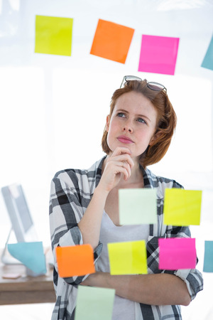 strawberry blonde: thoughtful hipster woman, standing in her office, reading notes on the all